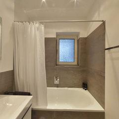 Badezimmer in Erdfarben mit Doppel-Waschtisch und Badewanne